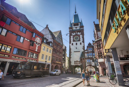 black forest: Editorial : FREIBURG IM BREISGAU, GERMANY, 07-08-2015: morning street with view at The Martinstor, one of the original city gates in Freiburg Editorial