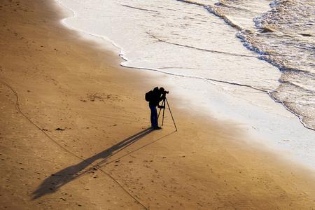 silhouet van de fotograaf op het strand Stockfoto