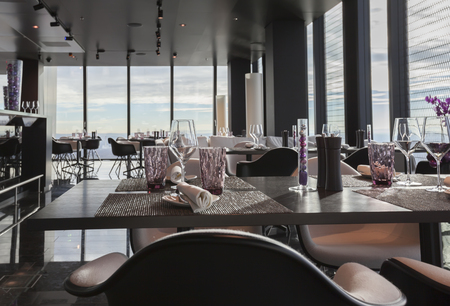 glasses on empty restaurant table in contemporary restaurant in sky Standard-Bild