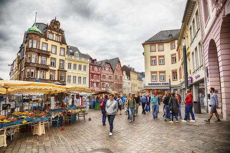 TRIER, GERMANY - 13 June 2018: people by medieval Marktkreuz Market Cross on Hauptmarkt Main Market square in Trier city