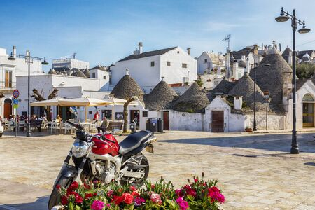 evening square in Alberobello town  with gabled (trullo) roofs, Puglia, Italy