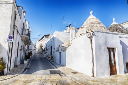 evening street in Alberobello town  with gabled (trullo) roofs, Puglia, Italy