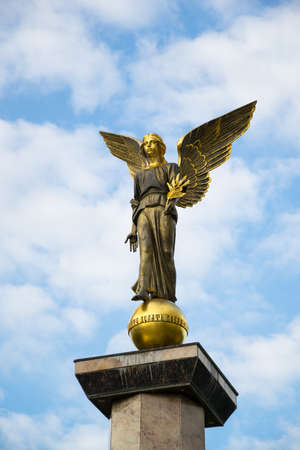 good heavens: Statue of an angel on a high pedestal against the sky.