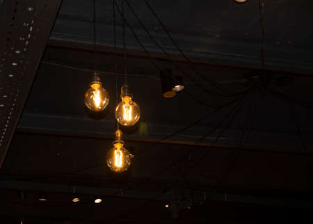 Lighting decor. Hanging Light Bulb in the dark room with copy space. Banco de Imagens