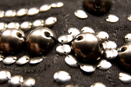 Silver shiny beads and sequins in vintage style are sewn on black coarse fabric.