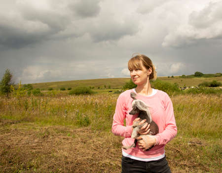 A middle-aged woman squints at the sun. A middle-aged woman in a pink sweatshirt enjoys a walk in nature and holds a small dog in her arms.