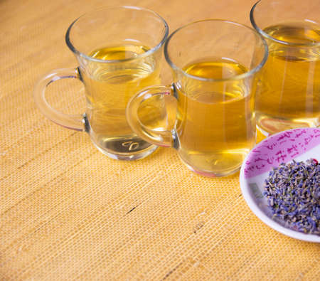 Herbal cold tea with lavender in glass cups on a yellow and red background.