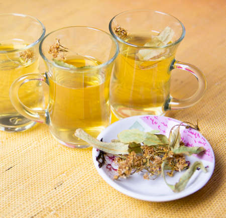Herbal linden tea, anti-inflammatory tea in glass glasses. Dry linden blossom on a saucer.