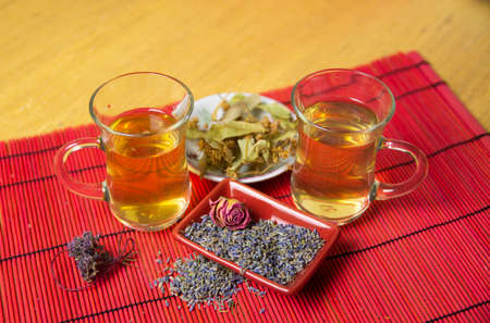 Herbal cold tea with lavender, linden and oregano in glass cups on a yellow and red background. Imagens