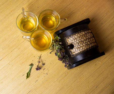 Herbal tea from a mixture of anti-inflammatory medicinal herbs in glass glasses. Herbs in a wooden box.