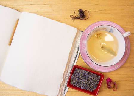 Handmade cotton notebook or sketchbook. Can be used as mocap. Nearby is a cup of herbal tea and dried flowers.