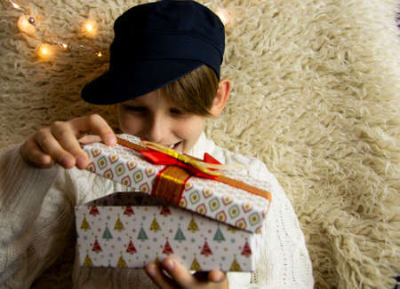 A 10-year-old European boy receives and enjoys a Christmas present.