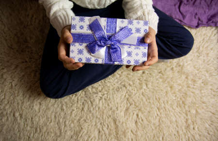 Christmas present in a beautiful box with a blue bow in childrens hands.