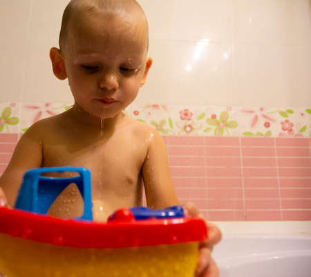 Happy little boy in the bathroom playing with plastic toy boat. Infant training and bathing. Hygiene and care for young children.