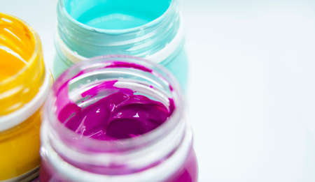 Jars of acrylic paint in blue, yellow, purple shades close-up. 版權商用圖片