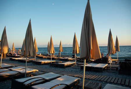 Empty sun loungers and covered beach umbrellas on an evening pebble beach in Sochi