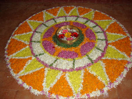 a traditional Indian art form using colored sand or powder with flowers to decorate floor