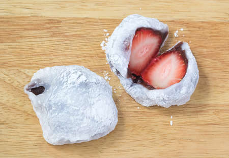 Japanese Traditional Dessert, Strawberry Mochi, Ichigo Daifuku or Japanese Rice Cake Made From Glutinous Rice Filled with Red Bean Paste on Wooden Board. photo
