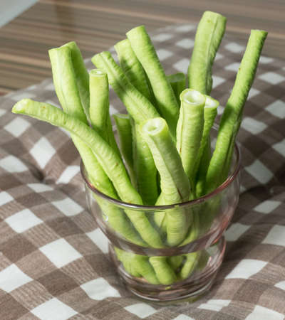 long beans: Vegetable, Pieces of Fresh Organic Chinese Long Beans or Yard Long Beans in A Glass.