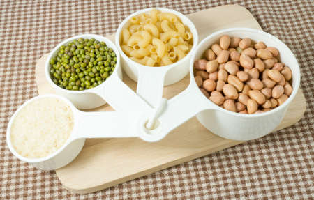 munggo: Foods High in Carbohydrate, Raw Pasta, Rice, Peanuts and Mung Beans in Plastic Measuring Cups. Stock Photo