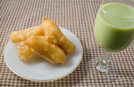 patongkoh: Snack and Dessert, Chinese Traditional Snacks Deep Fried Doughstick on A White Plate Served with Green Tea Soybean Milk.