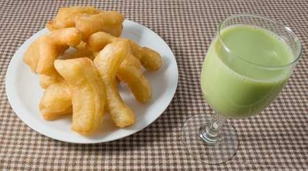 patongkoh: Snack and Dessert, Chinese Traditional Snacks Deep Fried Doughstick on White Plate Served with Green Tea Soybean Milk. Stock Photo