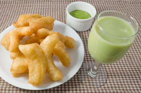 patongkoh: Snack and Dessert, Chinese Traditional Snacks Deep Fried Doughstick on A White Plate Served with Pandan Custard Dip and Green Soybean Milk.
