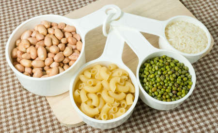 munggo: Foods High in Carbohydrate, Raw Pasta, Rice, Peanuts and Mung Beans in Plastic Measuring Spoons.