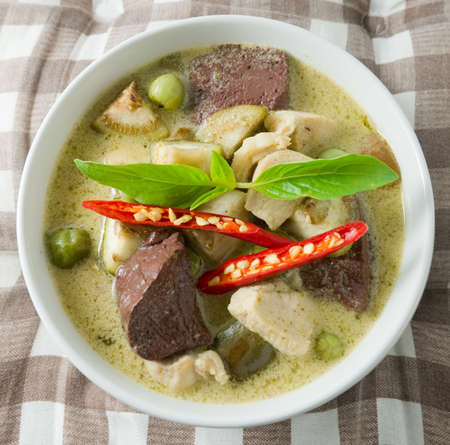 Delicious Thai Spicy Green Curry with Green Eggplant, Chicken and Coconut Milk, One of The Most Famous Curry Recipes in The World. photo