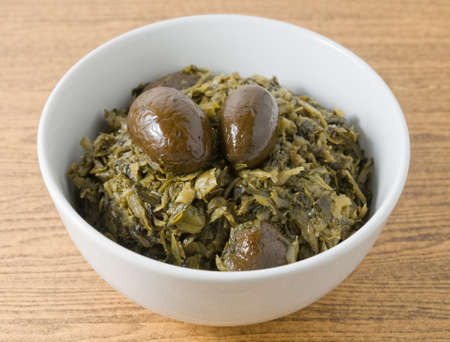 green cabbage: Chinese Traditional Food, A Bowl of Chopped Pickled Green Cabbage with Chinese Olives. Stock Photo