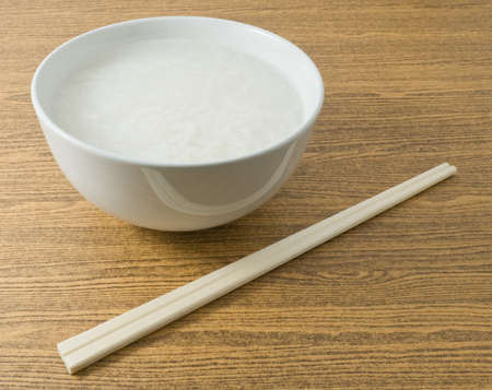 Asian Traditional Food, A White Bowl of Rice Porridge or Soft Boiled Rice with Wooden Chopsticks. Stock Photo