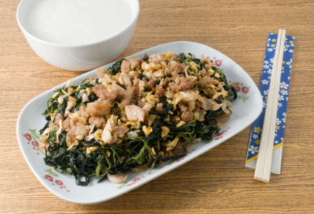 soy bean: Chinese Traditional Food, Stir Fried Jute Leaves or Mulukhiyah Leaves with Minced Pork, Garlics and Fermented Soy Bean Served with Soft Boiled Rice. Stock Photo