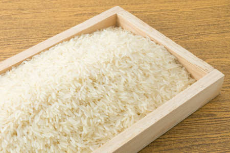 Cuisine and Food, Uncooked White Long Rice, Basmati Rice or Thai Jasmine Rice in A Brown Wooden Tray.