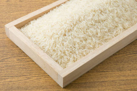 jasmine rice: Cuisine and Food, Uncooked White Long Rice, Basmati Rice or Thai Jasmine Rice in Wooden Tray.