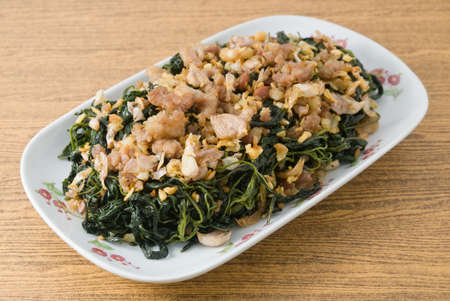 soy bean: Chinese Traditional Food, A Plate of Stir Fried Jute Leaves or Mulukhiyah Leaves with Minced Pork, Garlics and Fermented Soy Bean.