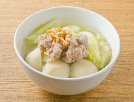 Thai Cuisine and Food, A Bowl of Lettuce with Minced Pork and Fish Meat Ball Soup Topping with Fried Garlic. 免版税图像