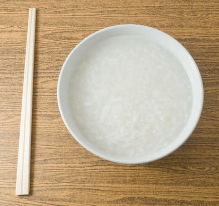 Asian Traditional Food, A Bowl of Asian Soft Boiled Rice or Rice Porridge with Wooden Chopsticks.
