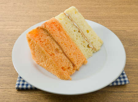 flavorings: Snack and Dessert, Vanilla and Orage Chiffon Cake Made With Butter, Eggs, Sugar, Flour, Baking Powder and Flavorings on A White Dish. Stock Photo