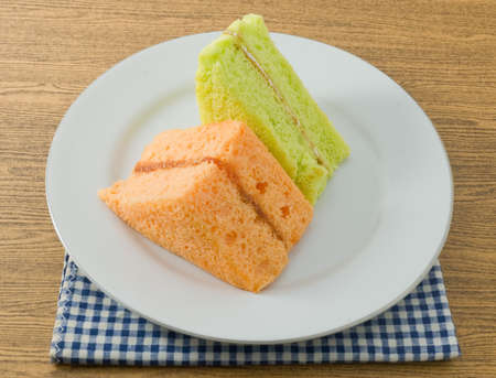 flavorings: Snack and Dessert, Pandan and Orange Chiffon Cake Made With Butter, Eggs, Sugar, Flour, Baking Powder and Flavorings on A White Dish.