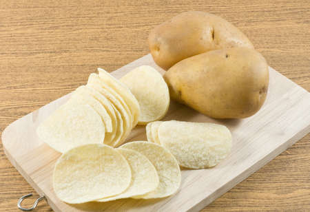 russet potato: Snack Food, Potato Tuber with Potato Chips or Crisp on A Wooden Tray.