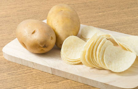 russet potato: Snack Food, Potato Tuber with Potato Chips or Crisp on Wooden Cutting Board.
