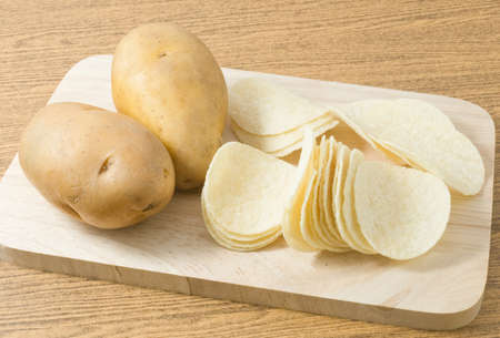 russet potato: Snack Food, Potato Tuber with Potato Chips or Crisp on Wooden Board.
