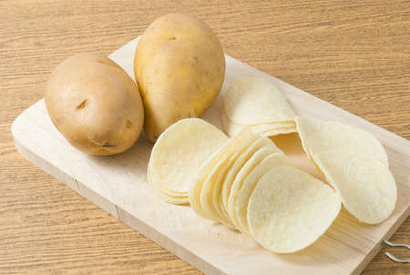 russet potato: Snack Food, Potato Tuber with Potato Chips or Crisp on Cutting Board.