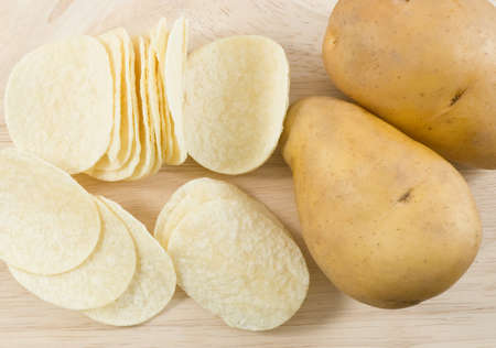 russet potato: Snack Food, Top View of Potato Tuber with Potato Chips or Crisp on A Wooden Cutting Board.