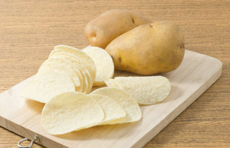 russet potato: Snack Food, Potato Tuber with Potato Chips or Crisp on A Wooden Cutting Board.
