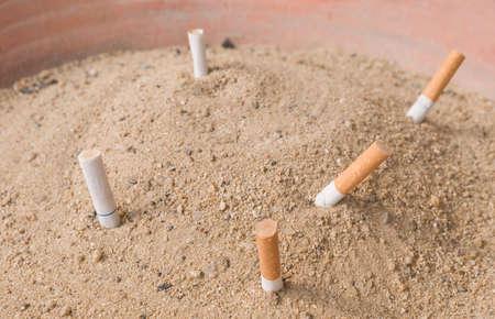 ciggy: Cigarette Butts and Ash in Public Terracotta Ashtray Big Tray. Stock Photo
