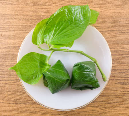 betel leaf: Thai Traditional Snack and Dessert, Top View of Miang Kum or Sweet and Spicy Betel Leaf Wrap Filled with Coconut, Peanuts, Dried Shrimp and Chiles with Lime Sauce.