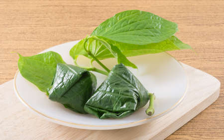 chiles secos: Thai Traditional Snack and Dessert, Miang Kum or Sweet and Spicy Betel Leaf Wrap Filled with Coconut, Peanuts, Dried Shrimp and Chiles with Lime Sauce. Foto de archivo