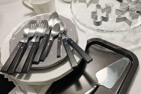 special occasions: Kitchen Utensil, Ceramic Plates, Coffee Cup, Silverware, Cake Spatula and Cookie Cutters Preparing for Special Occasions. Stock Photo