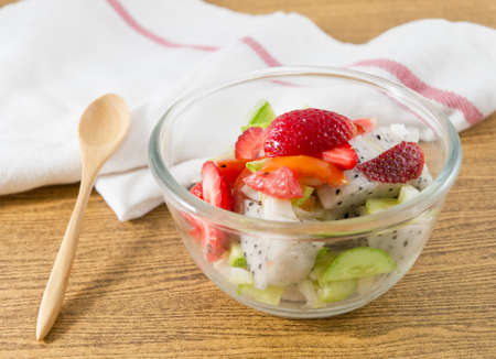 cuke: Glass Bowl of Delicious Fruits Salad, Strawberries and Dragon Fruit with Cucumbers and Tomatoes. Stock Photo